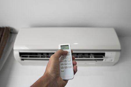 Mans Hand mit Fernbedienung. Hand, die rc hält und die Temperatur der Klimaanlage an einer weißen Wand einstellt. Komforttemperatur im Innenbereich. Gesundheitskonzepte und Energieeinsparungen.