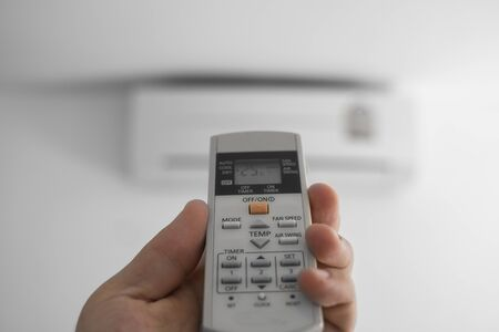 Mans hand using remote controler. Hand holding rc and adjusting temperature of air conditioner mounted on a white wall. Indooor comfort temperature. Health concepts and energy savings.