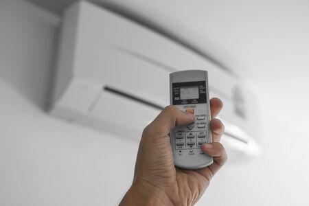 Mans mano con control remoto. Mano sujetando rc y ajustando la temperatura del aire acondicionado montado en una pared blanca. Temperatura de confort interior. Conceptos de salud y ahorro energético. Foto de archivo