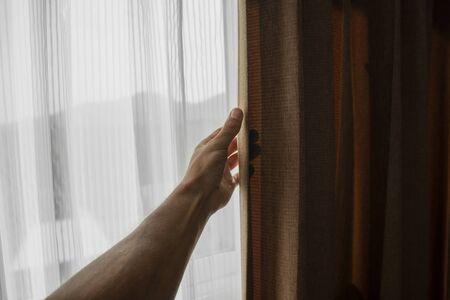 Männer Hand öffnen Vorhang im Schlafzimmer.