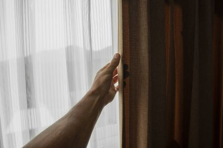 Men hand opening curtain in bed room.