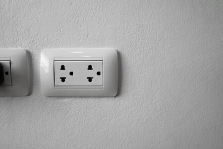 White universal electricity sockets plug on a white wall.