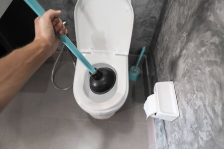 Toilet repair by hand with a Toilet Plunger. Plumbing. A plumber uses a plunger to unclog a toilet. Toilet Plunger.
