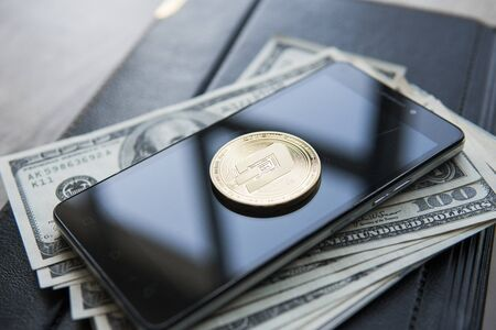 Golden Dash Cryptocurrency coin on a pile of US dollars and smartphone notebook. Cash money and crypto currency concept. Virtual. Exchange. Bussiness, commercial. 版權商用圖片