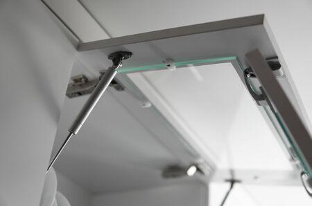 Chrom-Schrankschwingtürscharnier und Türpumpe, eingebaute Möbelbeschläge für die Küche. Nahaufnahme des modernen Clipscharniers und der Türpumpe des Möbelschranks.