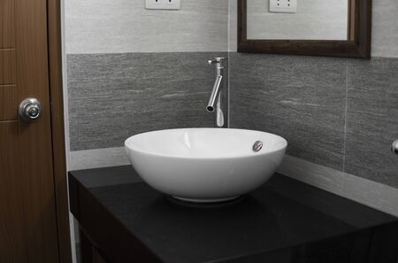 Bathroom interior with white round sink and chrome faucet in a modern bathroom.