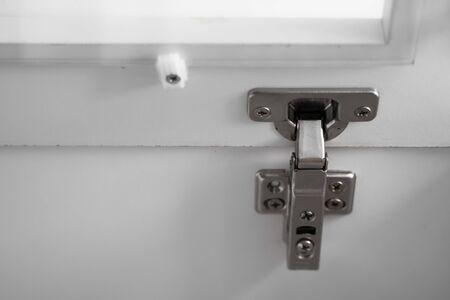 Charnière de porte battante d'armoire chromée, intégrée dans la quincaillerie de meubles pour armoire, placard ou cuisine. Gros plan de la charnière clip moderne de l'armoire de meubles.