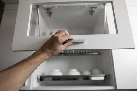 Hand holds the door of the dryer with utensils. Dish drying metal rack with white clean plates. Traditional comfortable kitchen. Open white dish draining closet with wet dishes of plates, bowls.