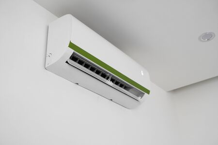 Air conditioner mounted on a white wall in the living room or bedroom. Indooor comfort temperature. Health concepts and energy savings.