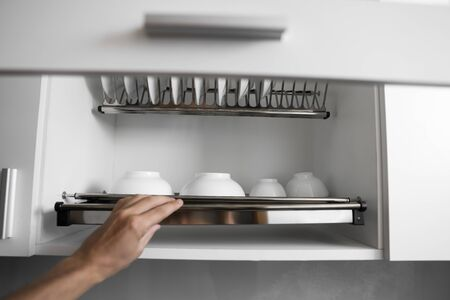 Dish drying metal rack with big nice white clean plates. Traditional comfortable kitchen. Open white dish draining closet with wet dishes of glass and ceramic, plates, bowls drying inside on rack.