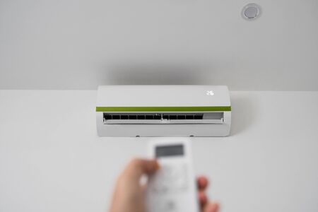 Mans hand using remote controler. Hand holding rc and adjusting temperature of air conditioner mounted on a white wall. Indooor comfort temperature. Health concepts and energy savings. 写真素材