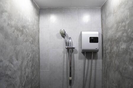 Chauffe-eau électrique instantané sans réservoir installé sur un mur de carreaux gris avec sortie de tuyau d'entrée et de sortie et système de disjoncteur de sécurité elcb et douche argentée.