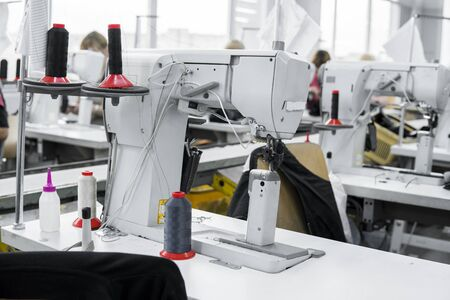 Professional sewing machine with black thread on a shoes factory Stock Photo