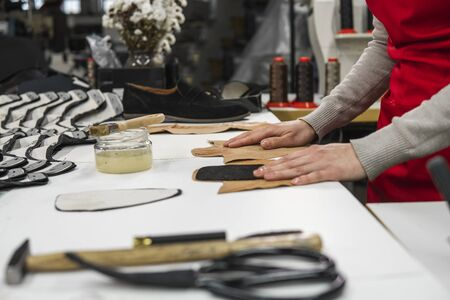 Shoemaker is adding glue with a brush to some pieces of leather that will be used to make shoes. The cobbler is working on his desk in his workshop