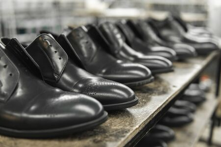A lot of new black shiny shoes on a shelf. Shoe factory, finished goods warehouse Banco de Imagens