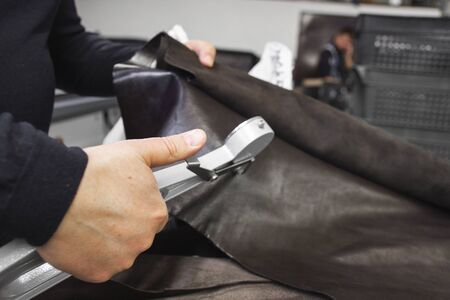 Mens hands use Leather thickness gauge on with a natural brown leather. Preparing of the raw materials for manufacture of bags, shoes, clothing and accessories Stockfoto