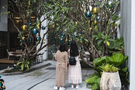 Two girls is standing near decorated Christmas tree with a blue and gold toys and beautiful blue butterfly toy. Holidays. Preparation for New Year and Christmas