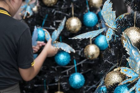 Decorated Christmas tree with a blue and gold toys and beautiful blue butterfly toy. Holidays. Preparation for New Year and Christmas