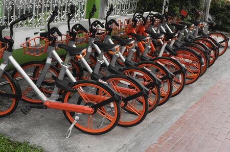 Street transportation orange hybrid rent bicycles with electronic form of payment for traveling around the city stand in row on rental network parking lot waiting for cyclists to make bike trip.