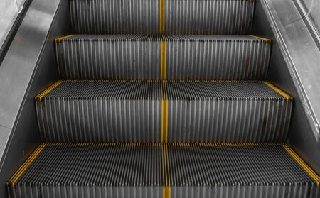 Ditry stairs on Escalator with yellow strips