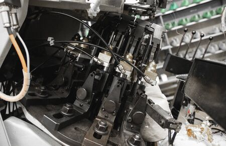 Man use special machine tool for making a shoes. The conveyor on a shoes factory with shoe and sole. Mass production of footwear.