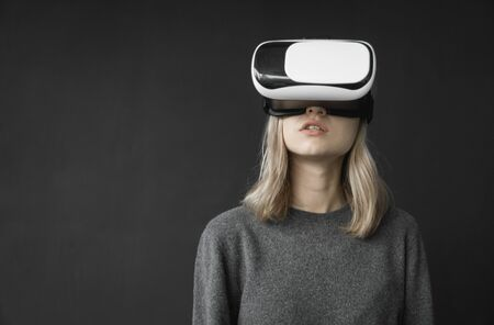Young woman wearing virtual reality goggles headset, vr box. Connection, technology, new generation, progress concept. Girl trying to touch objects in virtual reality.