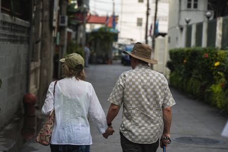Back view of well-dressed senior couple aged man and woman in hats walking arm-in-arm in town.