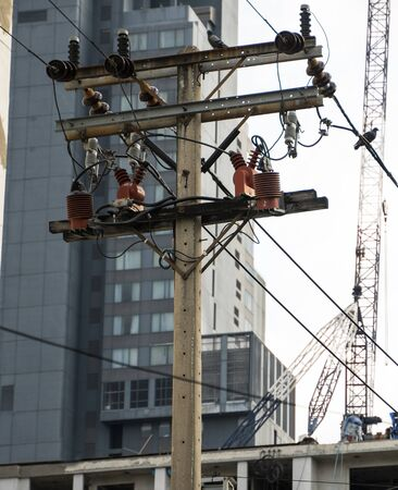 A high-voltage electricity pylons against buildings in the city. Фото со стока