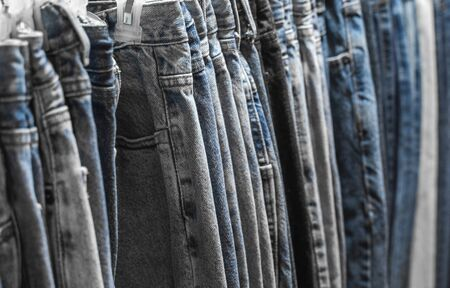 Fashion pants and jeans on the rack in clothing store. Sale, shopping, fashion, style concept. Jean Pants Hang on Shelf . Close up shot Vintage Denim jeans stack on shelves collection in store.