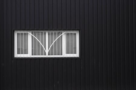Black and white Corrugated metal sheet texture surface on a building wall with windows. Galvanize steel background