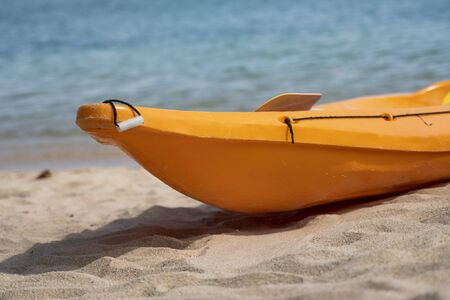 Two colorful orange kayaks on a sandy beach ready for paddlers in sunny day. Several orange recreational boats on the sand. Active tourism and water recreation