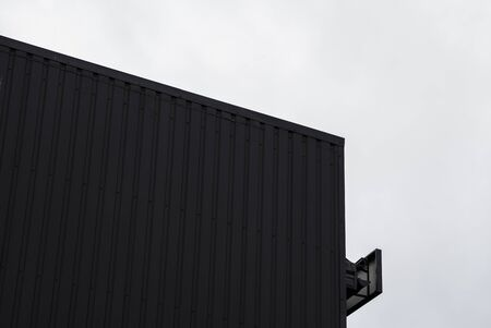 Black and white Corrugated metal sheet texture surface on a building wall with a cloudy sky. Galvanize steel background