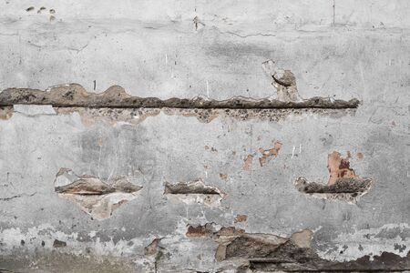 Cracked concrete grey wall covered with gray cement texture as background can be used in design. Dirty concrete texture with cracks and holes