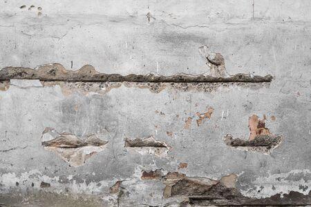 Gebarsten betonnen grijze muur bedekt met grijze cementtextuur als achtergrond kan in het ontwerp worden gebruikt. Vuile betontextuur met scheuren en gaten