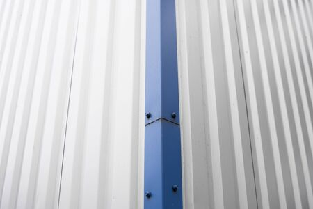 Metal corrugated sheets on a building with a blue metal corners. White aluminium metal corrugated roof or wall sheets on a factories and industrial buildings.