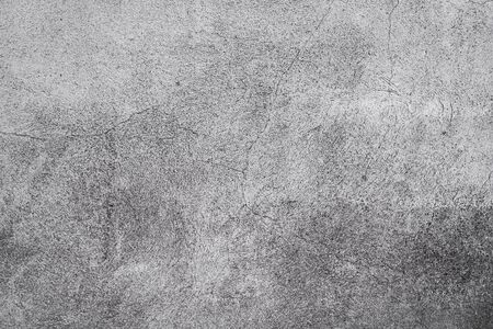 Cracked concrete grey wall covered with gray cement texture as background can be used in design. Dirty concrete texture with cracks and holes.