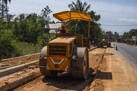 Road rollers working on the new roads construction site. Heavy duty machinery working on highway. Construction equipment. Compaction of the road Stock Photo