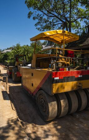 Road rollers working on the new roads construction site. Heavy duty machinery working on highway. Construction equipment. Compaction of the road. 版權商用圖片