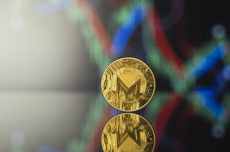 Monero and virtual money concept. Gold bitcoins with chart of growing and falling valuance of a cryptocurrency. Mining or blockchain technology. Mining of bitcoins online bussiness. Trading. Stock Photo