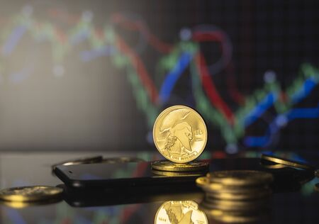 Titan bitcoin and virtual money concept. Gold Titan on a stack of coins with chart of growing and falling valuance of a cryptocurrency. Mining or blockchain technology. Stock fotó