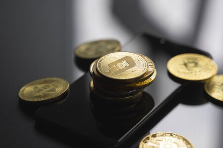 Stack of golden Dash bitcoin coin on a smartphone with a lot of bitcoins coins on a table. Virtual cryptocurrency concept. Mining of bitcoins online bussiness. Bitcoins trading.