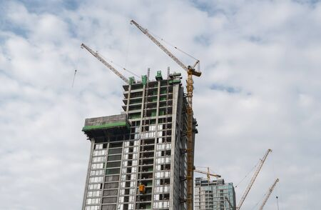 Construction site of building a high-rise building with a cranes against blue sky Archivio Fotografico