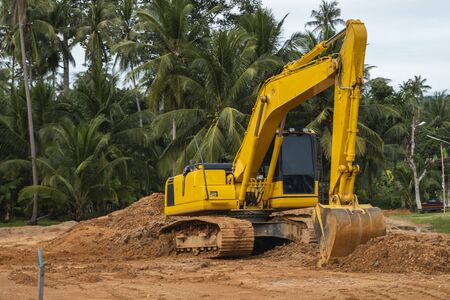 Yellow excavator on a construction site against blue sky. Heavy industry. Close up details of industrial excavator. Large tracked excavator standing on a orange ground with a palms on background