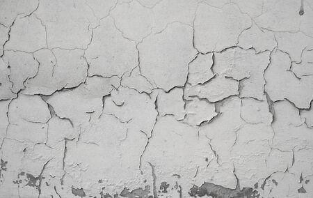Pęknięta betonowa szara ściana pokryta szarą teksturą cementu jako tło może być wykorzystana w projektowaniu. Brudna tekstura betonu z pęknięciami i dziurami