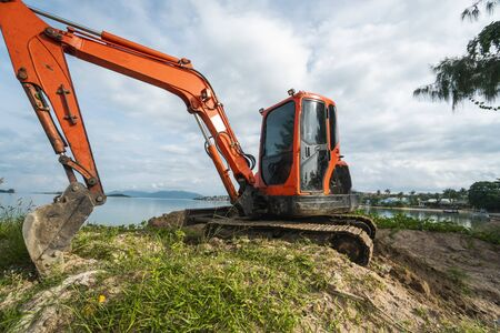 Small orange excavator on a ground against blue sky and sea for a works on construction site. Small tracked excavator standing on a ground with a blue sea on background. Heavy industry