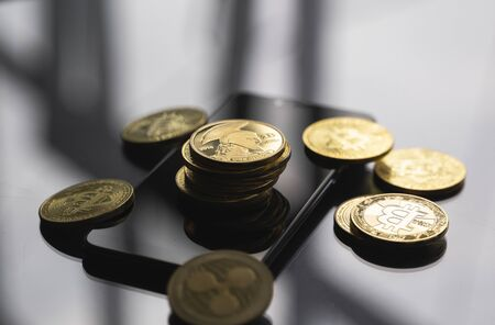 Stack of golden Titan bitcoin coin on a smartphone with a lot of bitcoins coins on a table. Virtual cryptocurrency concept. Mining of bitcoins online bussiness. Bitcoins trading
