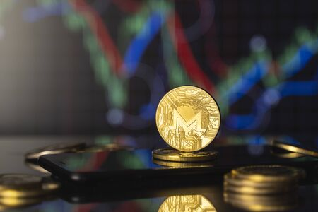 Monero and virtual money concept. Gold monero bitcoins on a stack of coins with chart of growing and falling valuance of a cryptocurrency. Mining or blockchain technology. Stock Photo