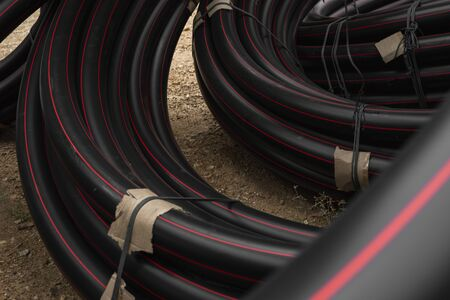 Black rubber or plastic pipes with a red lines as a construction material and equipment at building site. Using as a water pipe