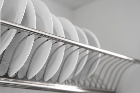 Dish drying metal rack with big nice white clean plates. Traditional comfortable kitchen. Open white dish draining closet with wet dishes of glass and ceramic, plates, bowls drying inside on rack