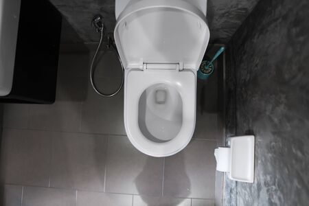 White hanging toilet seat on white toilet in the home bathroom with grey tiles in concrete style and toilet paper on the wall. Bathroom luxury interior.